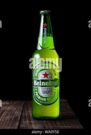 LONDON, UK - APRIL 27, 2018: Bottle of Heineken Lager Beer on dark wooden background. Heineken is the flagship product of Heineken International - Stock Photo
