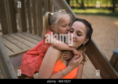 Happy mother playing with her little baby girl daughter and having fun - Young caucasian white mom wearing summer bright vivid color dress - - Stock Photo