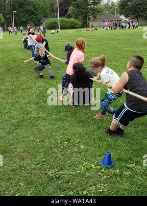 3rd grade students enjoying a fun game of tug-of-war. - Stock Photo