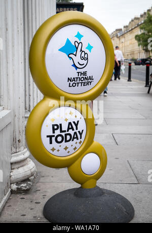 A gold National Lottery sign outside a newsagents in Bath - Stock Photo
