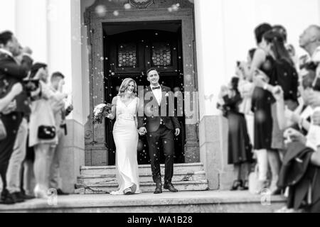 Newlyweds exiting the church after the wedding ceremony, family and friends celebrating their love with the shower of soap bubbles, custom undermining - Stock Photo