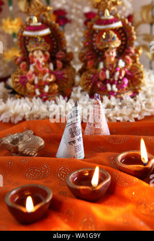 Diwali cracker wrapped with ten rupee banknote with oil lamp - Stock Photo