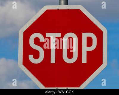 Stop sign in front of blue sky - Stock Photo