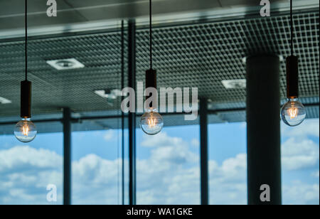 Close-Up Of Illuminated Light Bulbs Hanging In Coffeehouse At Airport - Stock Photo
