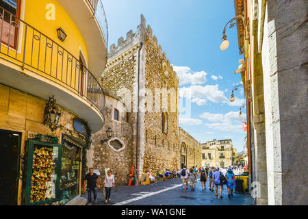 Tourists sightseeing on the main street, Corso Umberto, in the Mediterranean resort town of Taormina Italy on the island of Sicily - Stock Photo
