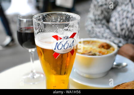Afternoon lunch at a Paris sidewalk cafe with a glass of Kronenbourg 1664 beer, a glass of red wine, and onion soup fondue. - Stock Photo