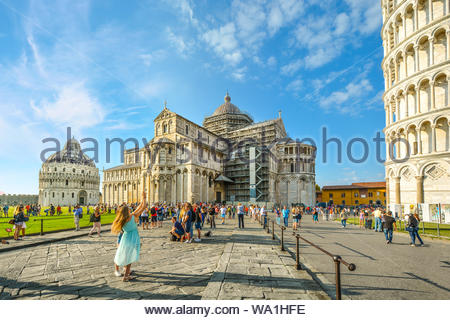 Two pretty female tourists pose in front of the Leaning Tower of Pisa with the Cathedral and Baptistery in view on the Square of Miracles in Pisa - Stock Photo
