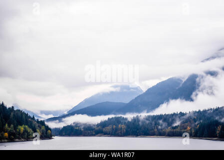 Fog and clouds covering forested mountains near lake in British Columbia, Canada. - Stock Photo