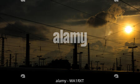 Catenary cables cross the sun in the background in the late afternoon - Stock Photo