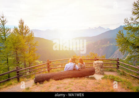 Happy couple sitting together on wood bench during sunset with view mountain - Stock Photo