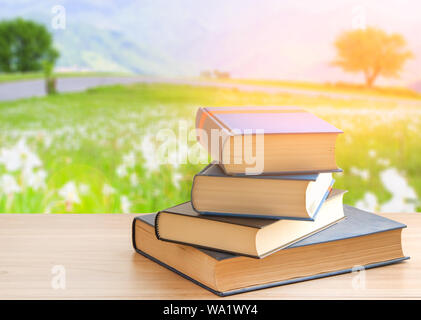 Book stack or pile of book on wooden table in nature background, back to school concept. - Stock Photo