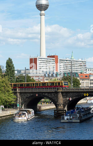 Tour boats on the Spree River going under the Stadtbahn Bridge by Museum Island with the TV Tower in the distance, Berlin, Germany. - Stock Photo