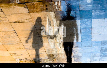Blurry reflection shadow silhouettes of  a young couple walking on a wet street  on a sunny summer day in old town stone pavement - Stock Photo