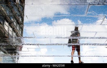 Reflection shadow silhouettes of  a young man walking on a wet street  on a sunny summer day in the city - Stock Photo