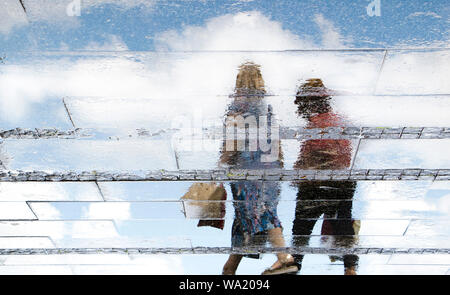 Reflection shadow silhouettes of  a two women walking on a wet street  on a sunny summer day in the city - Stock Photo