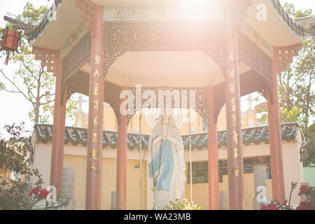 Ho Chi Minh City, Vietnam: Mother Mary statue in a Chinese style arbor lit with sun rays at Cha Tam Church (St. Francis Xavier Parish Church). - Stock Photo