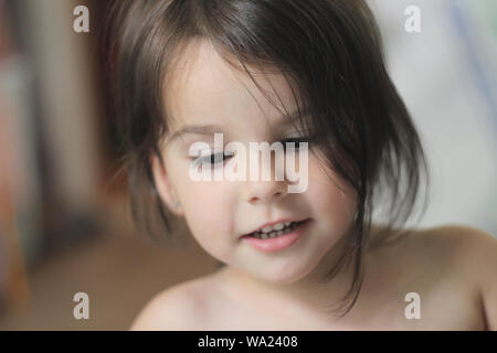 portrait of a beautiful little smiling girl with long brown hair and gaze down