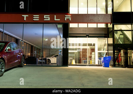Entrance of Tesla Showroom seen at night with an Tesla Model 3 parked outside and another on display inside. - Stock Photo
