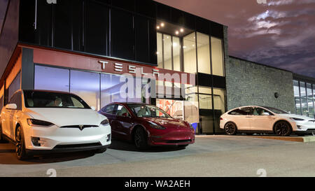 Entrance of Tesla Showroom and Service Center with Tesla Model 3 and two Tesla Model X's parked out front. - Stock Photo