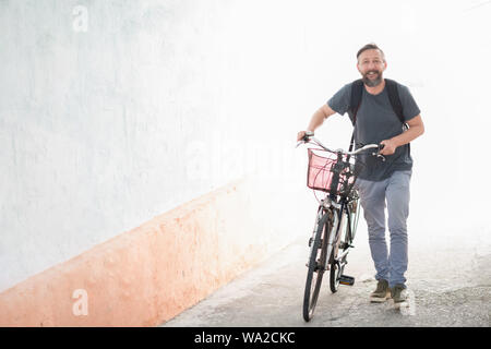 A young smiling stylish bearded hipster man with a backpack pushing a retro bicycle while walking on street - Stock Photo