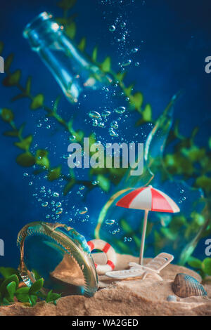Beach umbrella and deck chair underwater with bubbles and seaweeds. Drowning cities and global warming concept. Conceptual still life with miniatures.