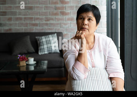 senior asia woman thinking and looking sideways, thinking and wondering
