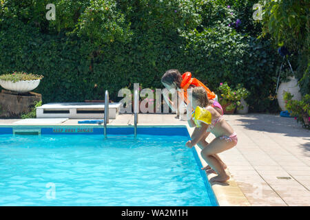 Two little girls jumping together in the pool; positive emotions, summer and fun - Stock Photo