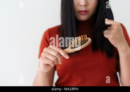 long loss hair on woman brush with and woman looking at her hair - Stock Photo
