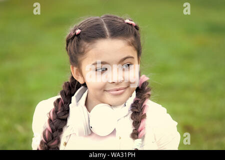 Healthy emotional happy kid relaxing outdoors. Get happy yourself. Girl modern headphones enjoy relax. Look on bright side. Secrets to raising happy child. Girl cute kid green grass background. - Stock Photo