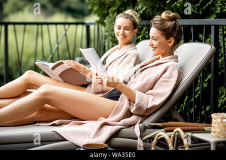 Two young women in bathrobes lying on the sunbeds, relaxing and spending time at the luxury SPA outdoors on the terrace - Stock Photo
