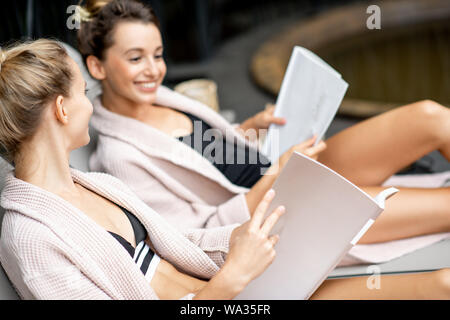 Two young women in bathrobes reading books while lying on the sunbeds at the SPA outdoors - Stock Photo