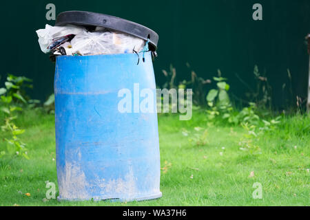 Full of rubbish blue bin at public playing park - Stock Photo