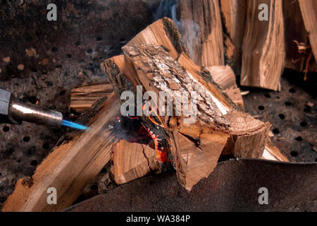 Fireplace kindling of chopped wood logs by gas torch. Method of firing at camping outdoor. Close up image of burning woods and flamethrower head - Stock Photo
