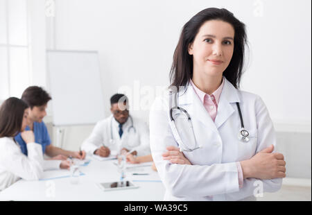 Female doctor looking at camera during meeting - Stock Photo