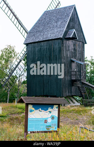 Old wooden windmill in Prietzen Germany with board showing the nature reserve at Guelper See - Stock Photo