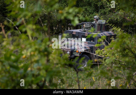 U.S. Army Soldiers from the Opposing Force (OPFOR), conceal their Humvee in the brush at the start of the culminating force on force exercise during Combined Resolve XII at Hohenfels Training Area, Germany Aug. 15, 2019. Combined Resolve is a biannual U.S. Army Europe and 7th Army Training Command-led exercise intended to evaluate and certify the readiness and interoperability of US forces mobilized to Europe in support of Atlantic Resolve. (U.S. Army photo by Sgt. Thomas Mort) - Stock Photo