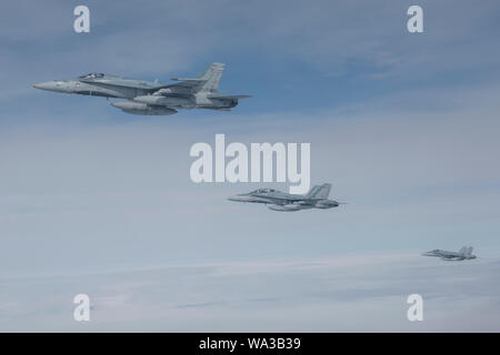 Royal Canadian Air Force CF-18 Hornets fly next to a CC-150T Polaris refueler over the Joint Pacific Alaska Range Complex during a sortie for Red Flag-Alaska 19-3 Aug. 15, 2019. RF 19-3 includes international participation from the Royal Air Force, the Royal Canadian Air Force, and the Royal Australian Air Force. RF-A is a Pacific Air Forces-directed field training exercise for U.S. and international forces flown under simulated air combat conditions. It is conducted on the JPARC with air operations flown out of Eielson Air Force Base and Joint Base Elmendorf-Richardson. (U.S. Air Force photo - Stock Photo