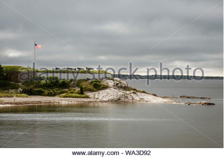Sun breaks through clouds to illuminate American flag, cannon, rocks and river - Stock Photo
