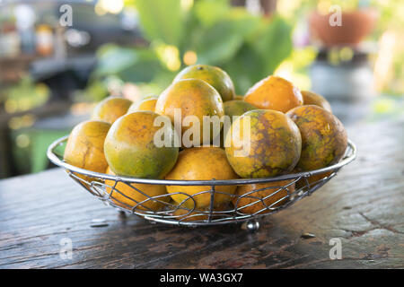 Close up tangerine in a silver metal basket placed on a wooden table with blurred background Stock Photo