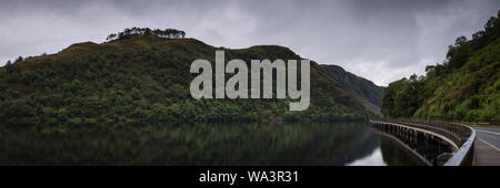 a road leads through a panoramic view of loch awe in scotland on a moody day with the trees on the hills reflecting on the water. - Stock Photo