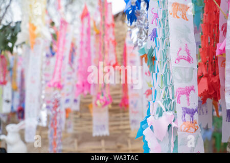 Prayer flags tung Hang with umbrella or Northern traditional flag hang on sand pagoda in the temple for Songkran Festival is celebrated in a tradition - Stock Photo