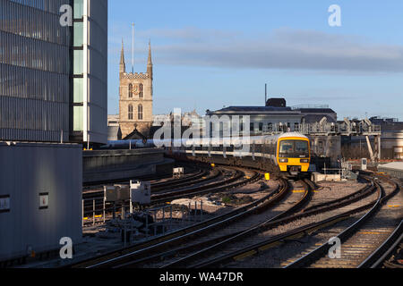 South Eastern trains class 465 trains passing London Bridge with Southwark cathedral behind - Stock Photo