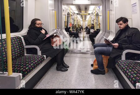 Passengers reading and ignoring each other sitting in silence on a London Underground district line train heading west from Earls Court - Stock Photo
