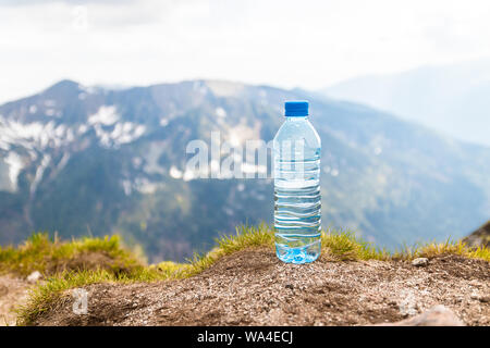 Pure water in plastic bottles on the stone against the background of a picturesque view Zakopane Tatra Mountains Kasprowy Wierch in the summer. Travel - Stock Photo