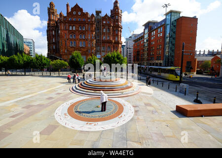 Full wide landscape view of Peterloo Memorial Manchester in blue skies and sunshine with Midland Hotel in background and multiple people interacting. - Stock Photo
