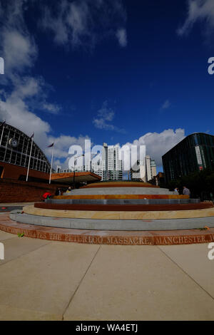 Portrait view of Peterloo Memorial Manchester in blue skies and sunshine with Manchester Central in background and people interacting. - Stock Photo