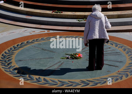 People interacting with Peterloo Memorial Manchester on a summers day casting their shadow across the monument and a bunch of flowers - Stock Photo