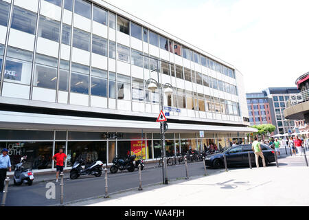 Frankfurt, Germany - July 06, 2019: Pedestrians and visitors strolling through Friedrich-Stoltze-Square with its business buildings and shopping malls - Stock Photo