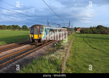 First Transpennine Express class 350 electric train on the west coast mainline in Lancshire with a Manchester to Glasgow train - Stock Photo