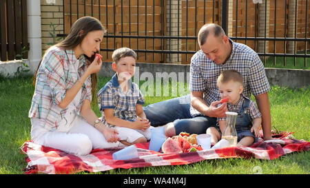 mother with loose brown hair sits with handsome father feeding sons with water melon on checkered blanket - Stock Photo